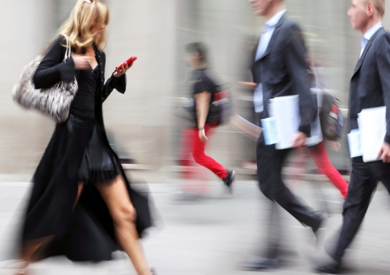 Woman walking through busy street with mobile phone