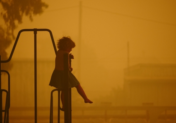 Girl on a climbing frame in sunlight filtered through thick bushfire smoke