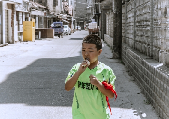 Boy eating an ice cream on an abandoned street in China