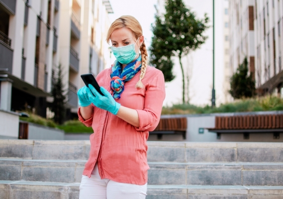 A woman wearing a protective mask and gloves uses a mobile phone