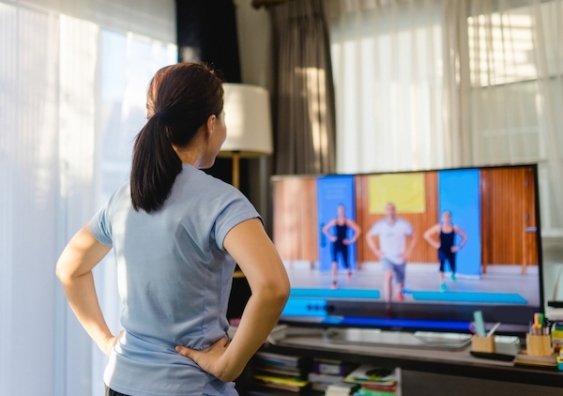 A woman follows a virtual exercise class at home