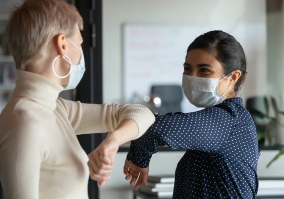 Two co-workers wearing masks and greeting each other in the office.