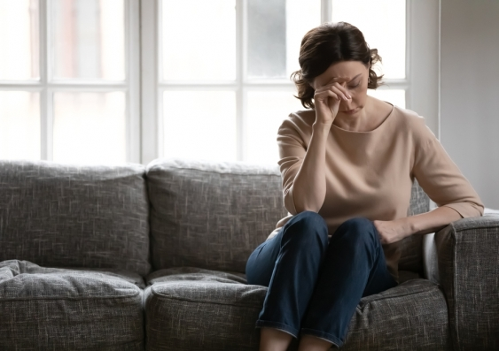 Woman sitting on lounge in pain