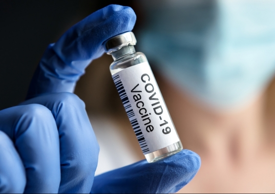 Doctor holds bottle with COVID-19 vaccine in laboratory