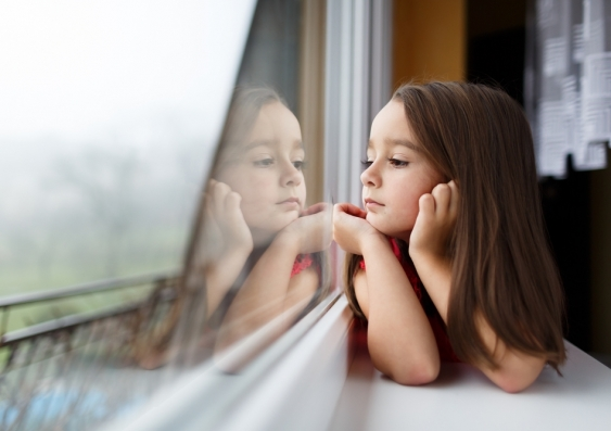 Young girl gazing out of a window