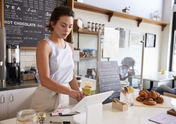 Waitress keys in an order on a screen in a sunlit cafe