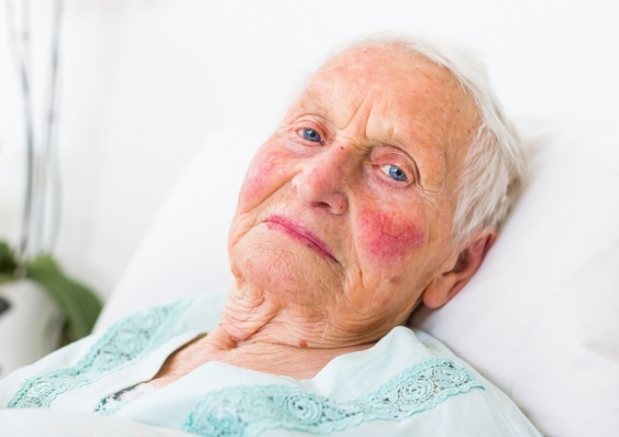 elderly woman lies on a hospital bed in her nightdress