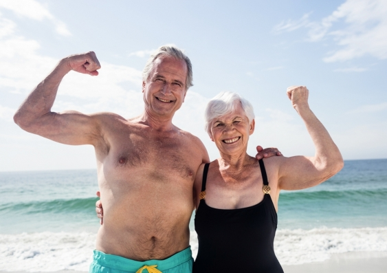 Smiling older couple flexing muscles at the beach