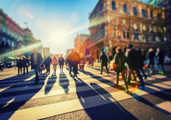 commuters walk through a busy sunny street