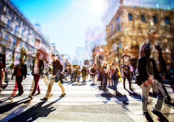 Crowds of people walking across a sunlit street