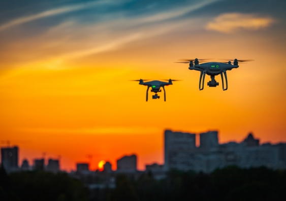 Two drones flying over a city