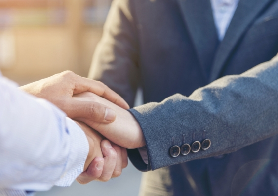 People dressed in corporate attire shaking hands.