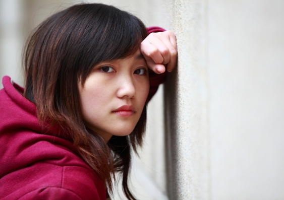 A young woman leans against a wall and looks straight ahead