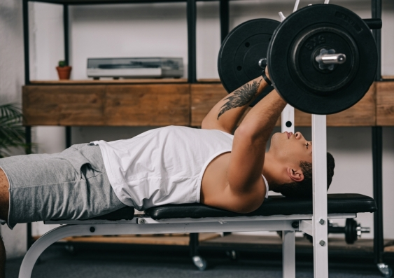 Side view of man bench-pressing weights