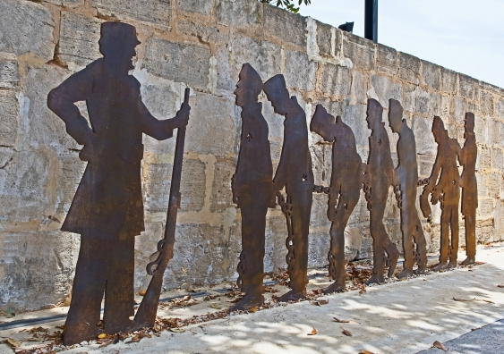 silhouettes of colonial convicts and an armed guard