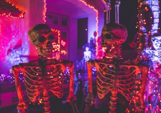 Two skeleton Halloween decorations in neon light