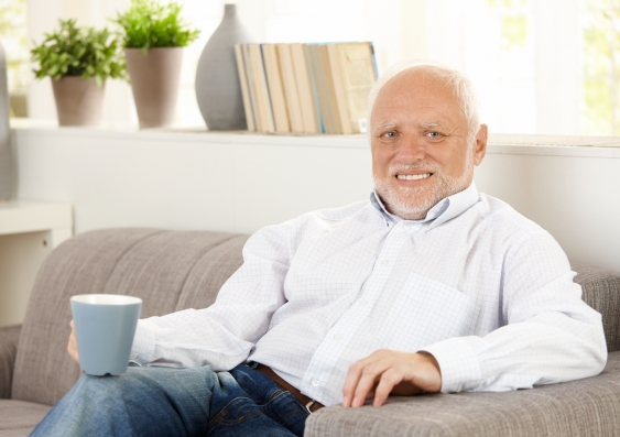 smiling elderly man having coffee at home sitting on a sofa