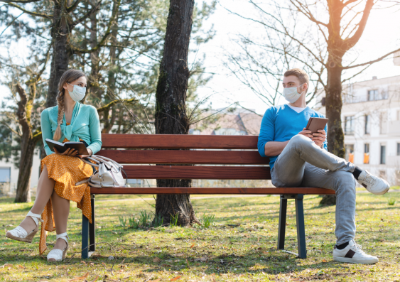 Two people sitting on a bench with books in hand, social distancing and wearing face masks during COVID-19.