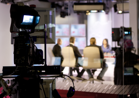 Media TV studio with focus on camera shooting a news production.