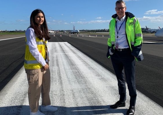 Manmeet Kaur and Geoff Culbert standing on a runway at Sydney Airport