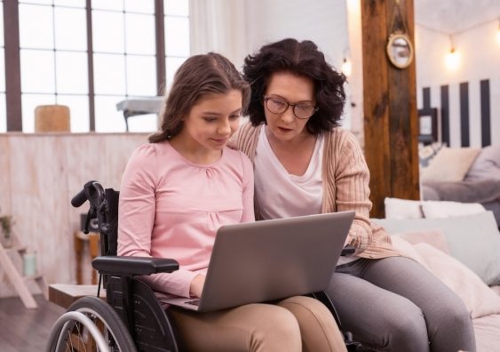 Teenage girl in wheelchair using a laptop next to her mother
