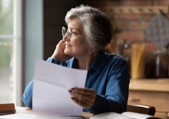 Thoughtful senior woman holding document smiles into the distance