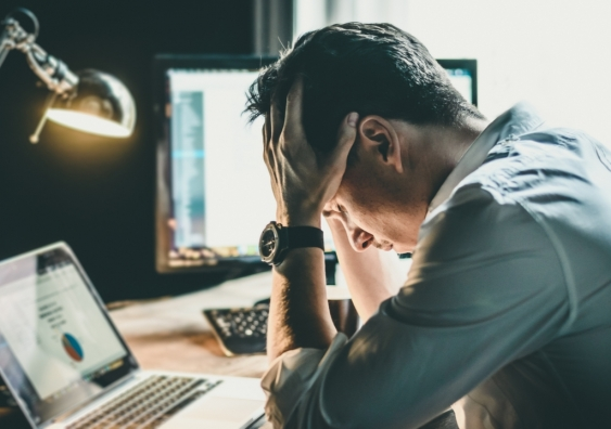 Stressed man holding his head in his hands working late into the night