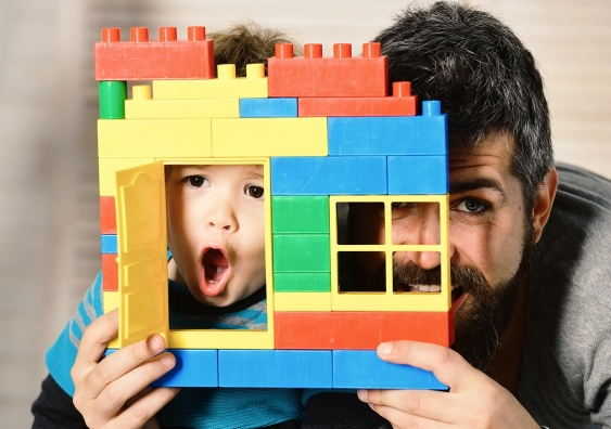a boy and man looking through the window of a small Lego house