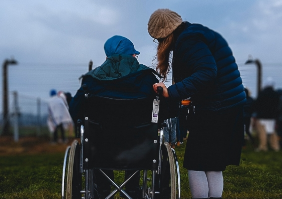 Woman talking to man in a wheelchair