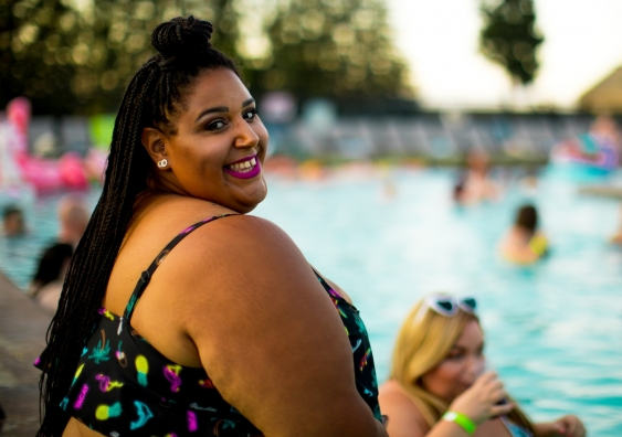 Smiling plus sized woman beside pool
