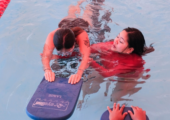 A swimming teacher with a student using a kickboard