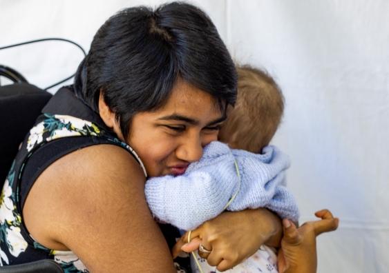 A woman hugs an infant