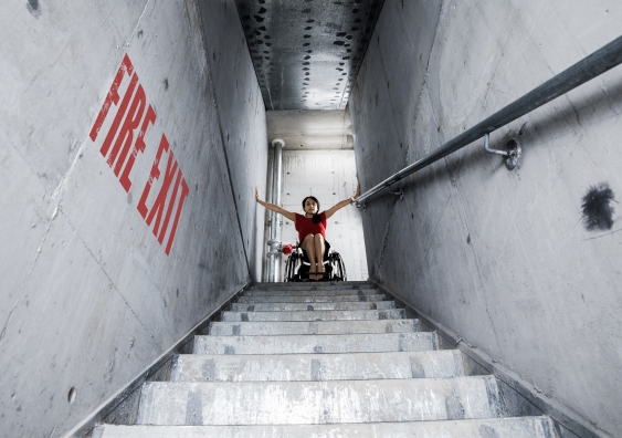 A woman in a wheelchair at the top of a fire exit flight of stairs