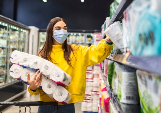 Woman buying multiple packs of toilet paper