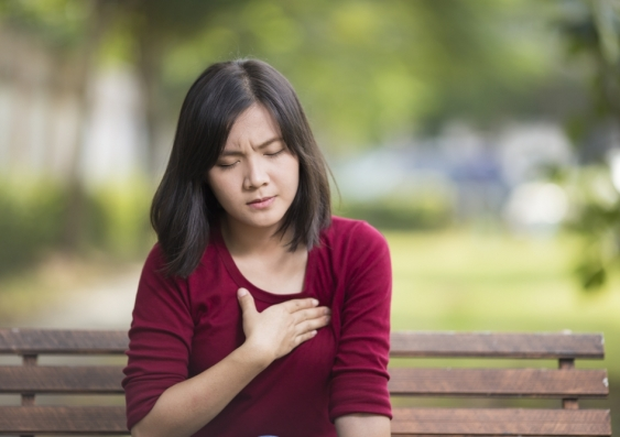 Woman on park bench clenching heart