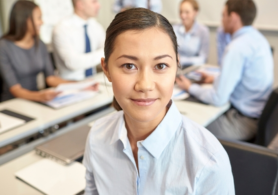 Woman in an office looks at camera while team meeting continues behind her