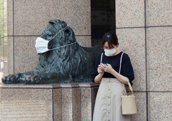 Woman stands next to a lion statue, both wearing face masks