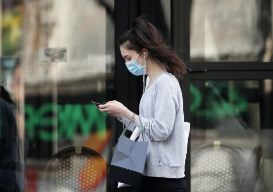 Woman wearing face mask using phone as she walks down the street
