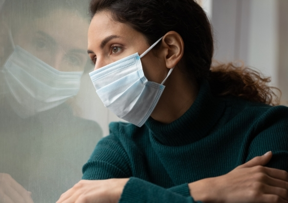 Woman wearing a face mask looking out of a window