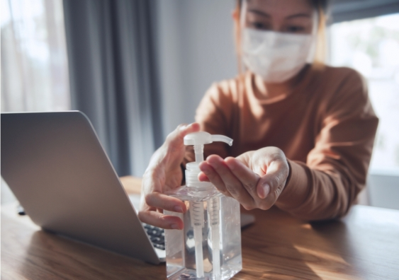 Woman working on a laptop wears protective mask