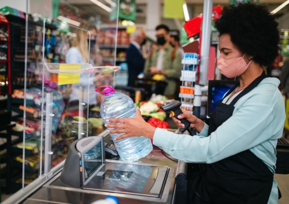 Woman working at grocery story checkouts scanning items while wearing face mask