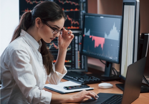 Woman working online with multiple computer screens examines stock index charts