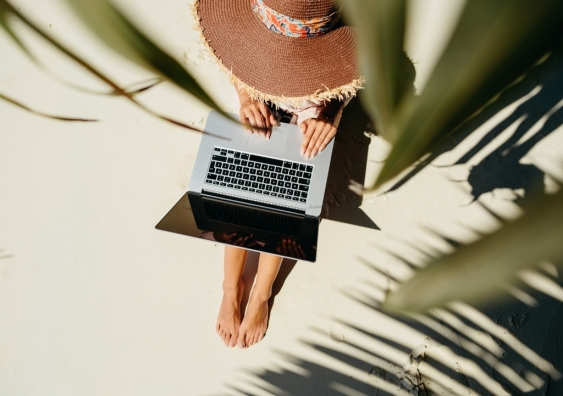 Woman working remotely on a laptop by the beach