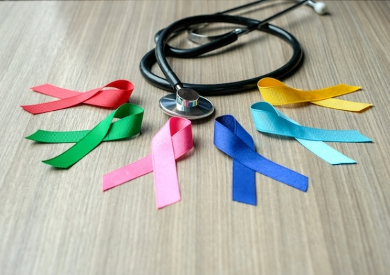 A collection of colourful charity ribbons signifying cancer awareness, pictured with a stethoscope.