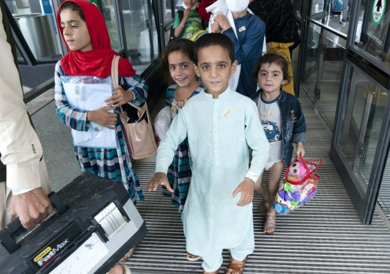 young afghan children leave an airport after leaving the country