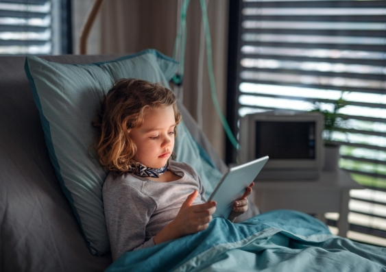 Young girl in hospital bed using an electronic tablet