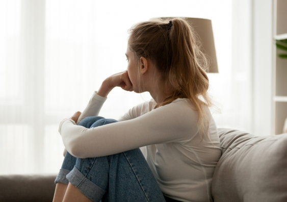 Young worried woman looking out the window