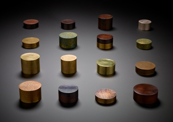 Art vessels crafted from brass, copper and silver arranged on a surface