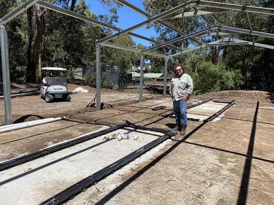 Trevor Evans stands under the frame of the soon-to-be built breeding facility