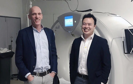 Two male doctors in front of a CT scanner